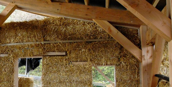 Straw bales being fitted to a Douglas fir frame to create an eco-house.