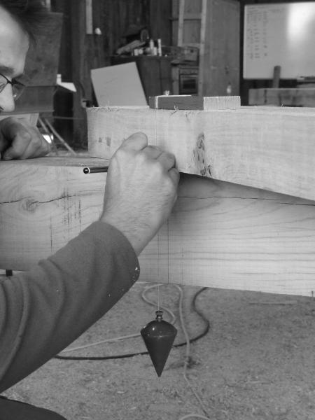 Traditional carpentry using a plumb bob.