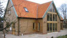 Oak framed house with direct glazing and oak weatherboarding.