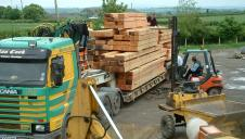 A lorry delivering timber to a framing yard.