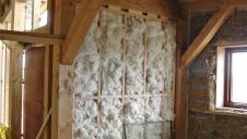 The interior of a Douglas fir framed house with a sheeps wool wall being built.