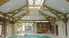Oak framed swimming pool with sling brace trusses and a lantern.