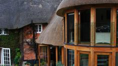 Round oak framed extension to a thatched listed building.