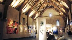 An exhibition under the oak roof at Place Barton Barn.