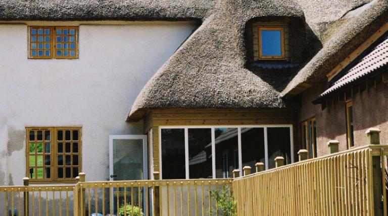 Restored Devon cob farmhouse with thatched roof.