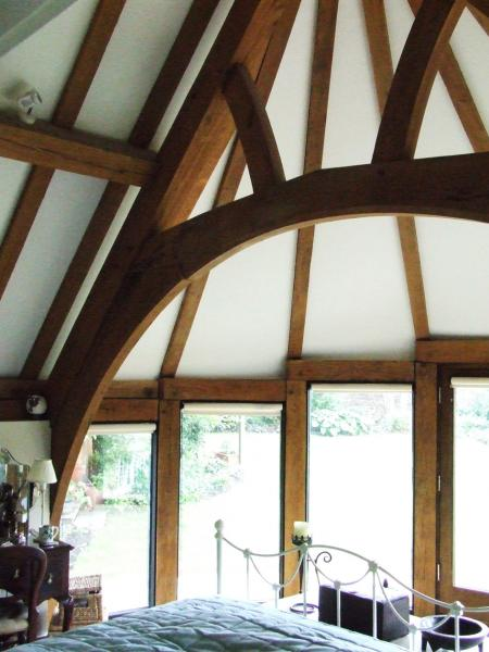 An oak framed bedroom with curved feature window.