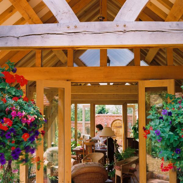 An oak framed garden room with hanging baskets.