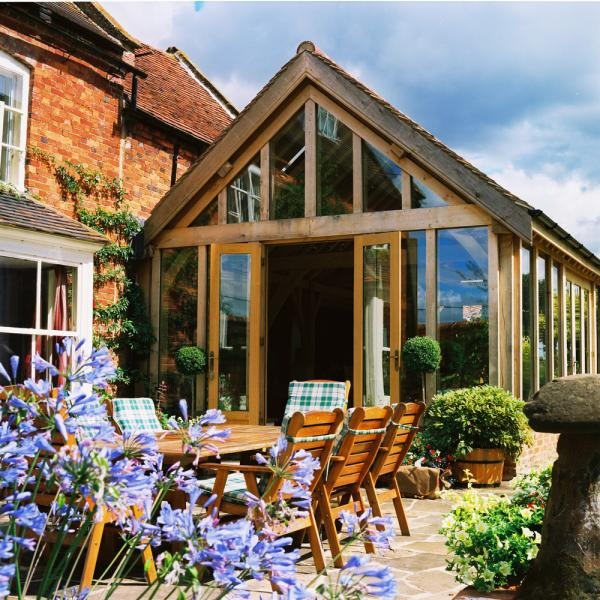 An oak framed garden room extension to a listed building with patio furniture outside.